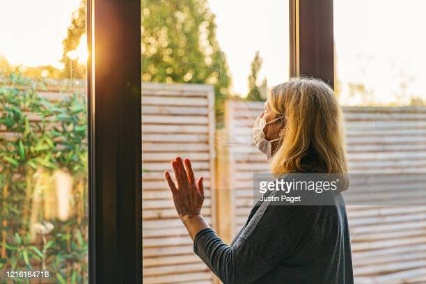 senior women with mask looking through window - sun stock pictures, royalty-free photos & images