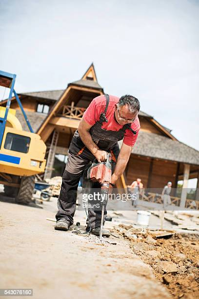 Senior worker demolishing the concrete with a drill.
