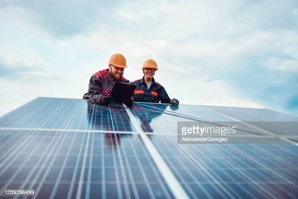 senior worker helping younger male measure solar panel dimensions - fuel and power generation stock pictures, royalty-free photos & images