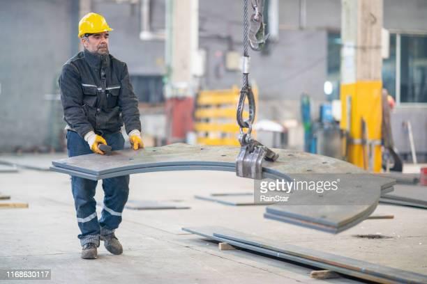 operaio anziano che tiene e lavora con il telecomando per il funzionamento della gru - sollevare foto e immagini stock