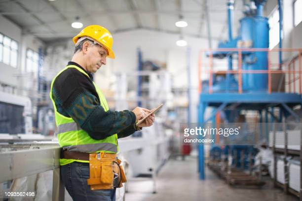 senior worker in the factory operating machines - inspector stock pictures, royalty-free photos & images
