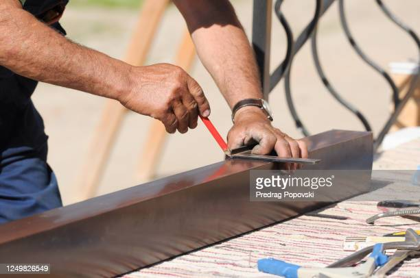 senior worker with dirty hands repairing gutter - kumanovo stock pictures, royalty-free photos & images