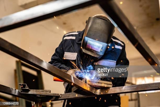 operaio senior che lavora con l'utensile di saldatura - ferro foto e immagini stock