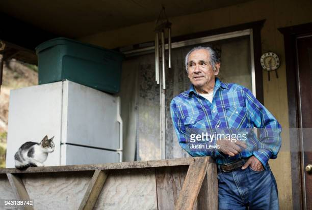 Senior Yurok Man Leans on Front Porch With Cat, Waiting for Fishing Friends to Arrive