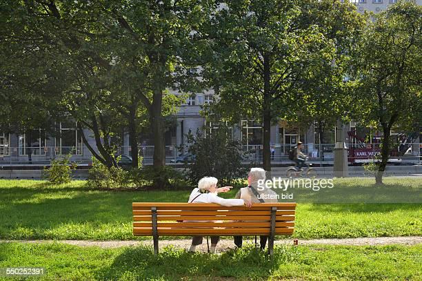 Seniorenpaar unterhält sich auf einer Parkbank an Frankfurter Allee in BerlinFriedrichshain