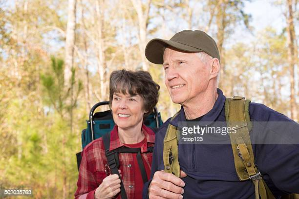 Seniors: Active senior couple hiking outdoors in forest. Nature.