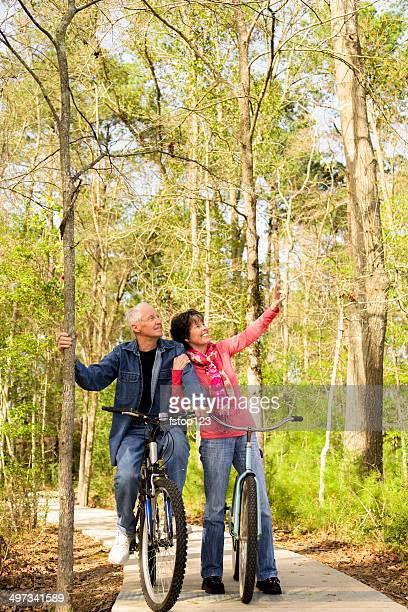 Seniors: Active senior couple outdoors riding bikes. Nature.
