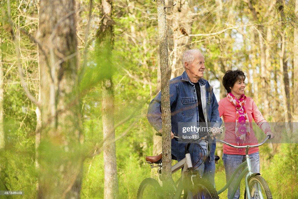 Seniors: Active senior couple outdoors riding bikes. Nature. : Stock Photo