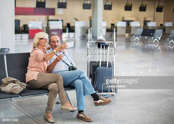Seniors ar airport taking a selfie