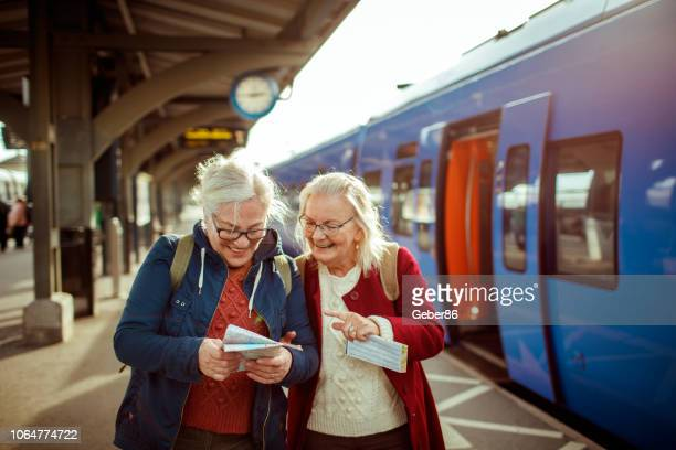 seniors at a trainstation - journey stock pictures, royalty-free photos & images