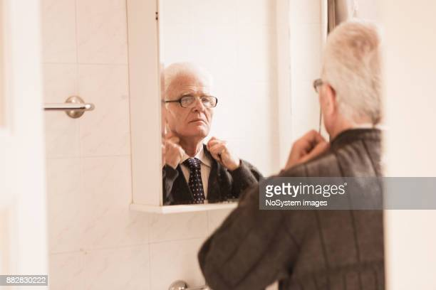seniors at home. senior man looking himself at the mirror, , getting dresses - adjusting necktie stock pictures, royalty-free photos & images