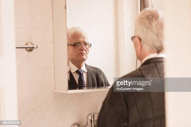 Senioren zu Hause. Senior woman selbst in den Spiegel schauen, immer Kleider