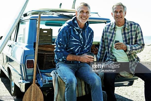 seniors at the beach surfing and hanging out - landvoertuig stockfoto's en -beelden