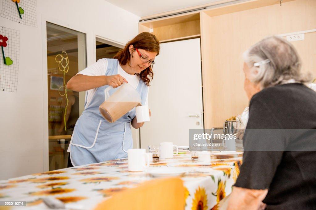 Seniorer på det äldreboende med frukost : Bildbanksbilder