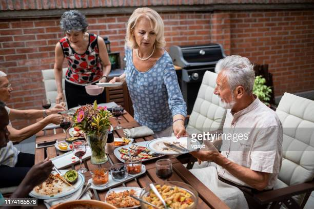 seniors cleaning dinning table after vegan bbq party - cleaning after party stock pictures, royalty-free photos & images
