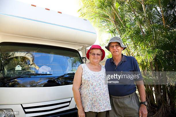 Seniors couple standing with motorhome RV waist up