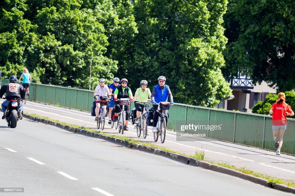 Seniors cycling on bridge over Ruhr : Stock Photo