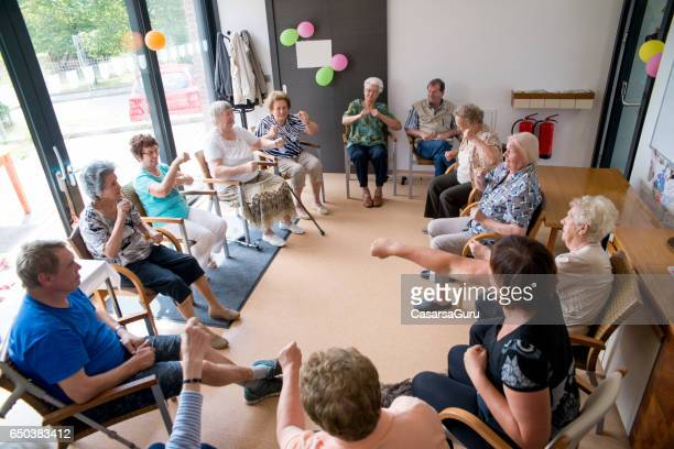 Seniors Doing Relaxation Exercises In The Elderly Day Care Center