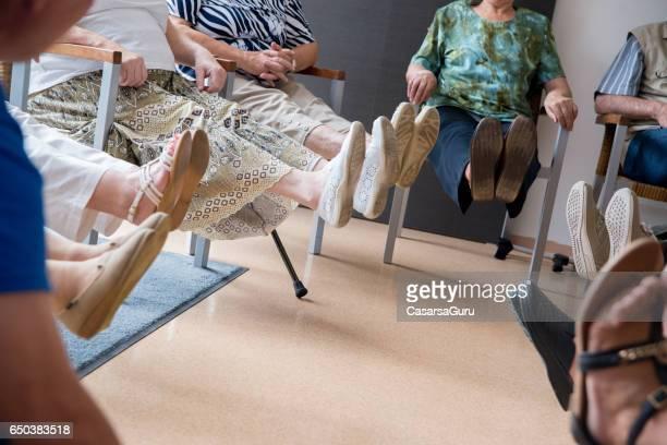 Seniors Doing Relaxation Exercises In The Elderly Day Care Center