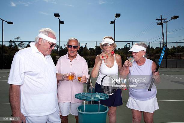 Seniors drinking on the tennis court