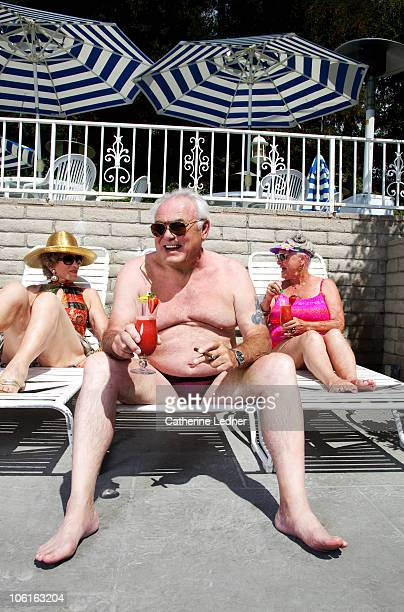 seniors enjoying drinks by the pool - old man in speedo stock photos and pictures