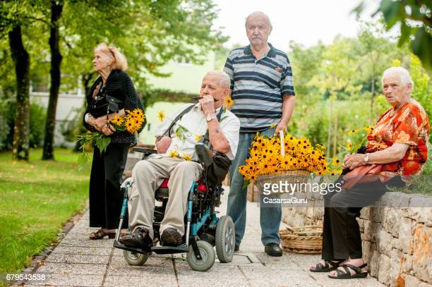 seniors  enjoying in the backyard of the retirement community - residential care stock photos and pictures
