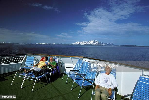 Seniors enjoying the sun on deck of the Coastal Express. For more than a century, the coastal steamer Hurtigruten has been the lifeline linking the...