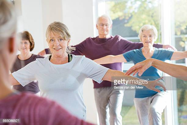 seniors following teacher in yoga exercise class. - standing on one leg stock pictures, royalty-free photos & images