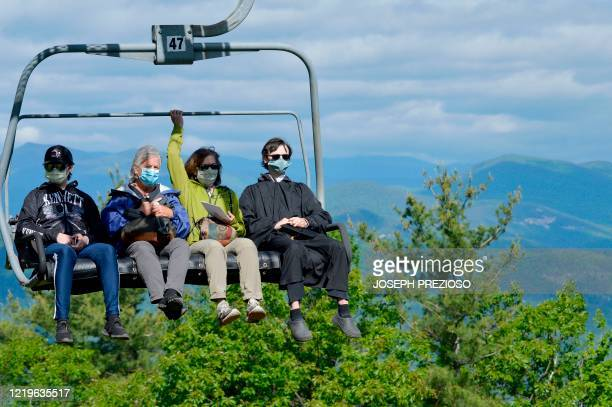 Seniors from Kenneth High School and family ride a ski lift to the summit of Cranmore Mountain in North Conway, New Hampshire, on June 13 for their...