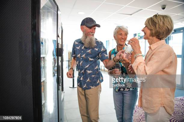 seniors getting a drink from a vending machine - vending machine stock photos and pictures