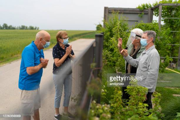 seniors greeting at garden fence with new handshakes - fence stock pictures, royalty-free photos & images