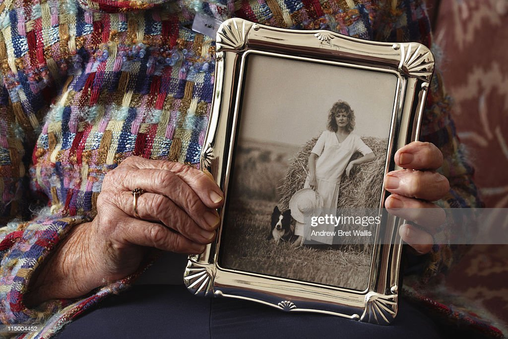 Senior's hands holding vintage photo of herself : Stock Photo