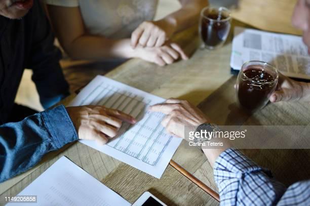 seniors' hands on financial documents - fondo pensionistico personale foto e immagini stock