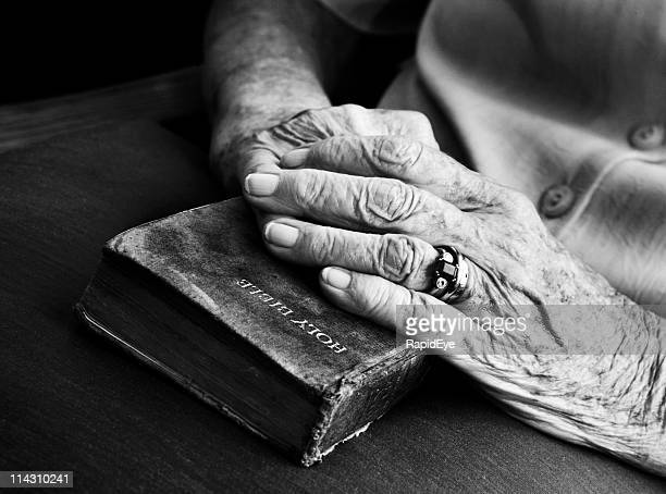 senior's hands on old bible - black and white hands stock pictures, royalty-free photos & images