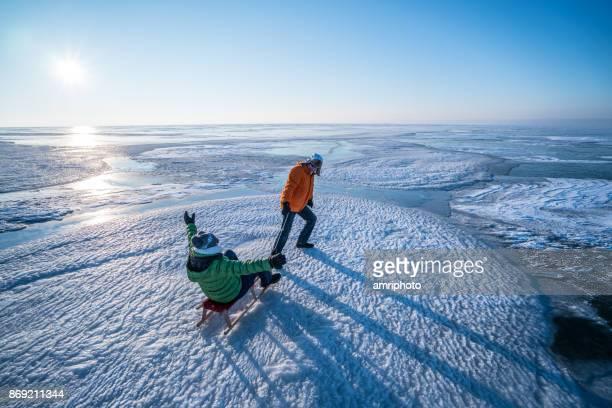 Aînés - heureux couple de personnes âgées avec la luge sur lac gelé