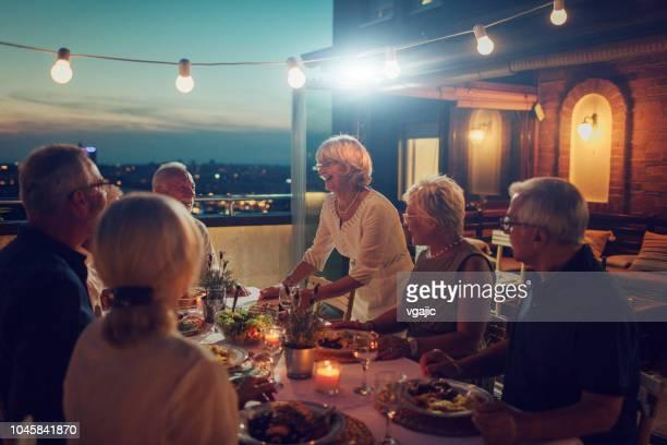 seniors having dinner on rooftop - evening meal imagens e fotografias de stock