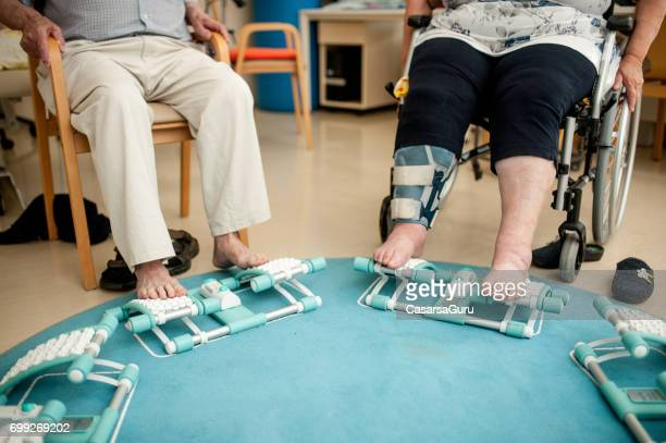 Seniors Having Foot Massage Using Foot Roller