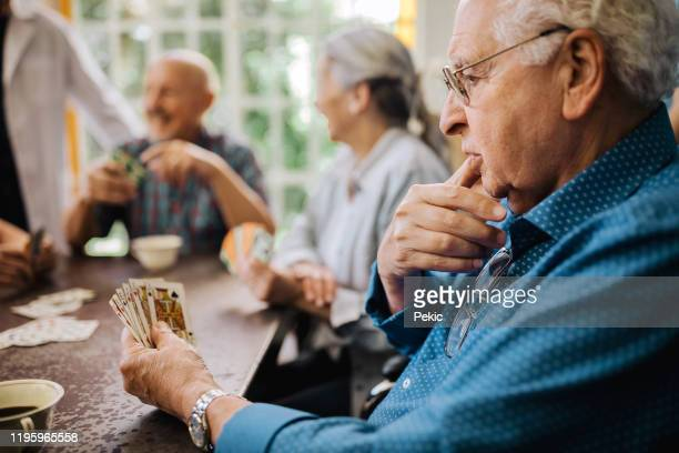 seniors having fun playing cards in nursing home - thinking of you card stock pictures, royalty-free photos & images