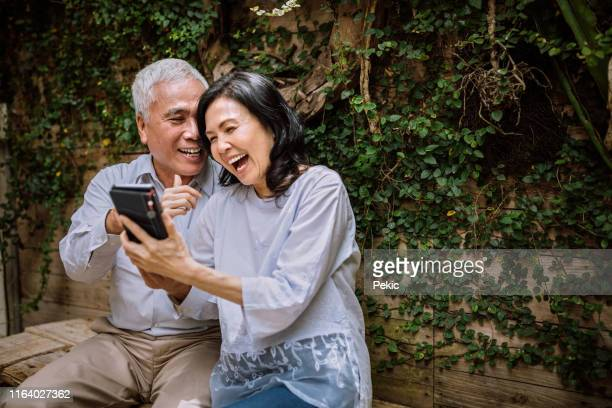 seniors having video call on phone with their family - baby boomer stock pictures, royalty-free photos & images