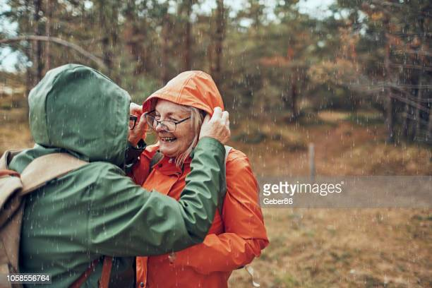 seniors hiking in the rain - senior adult stock pictures, royalty-free photos & images