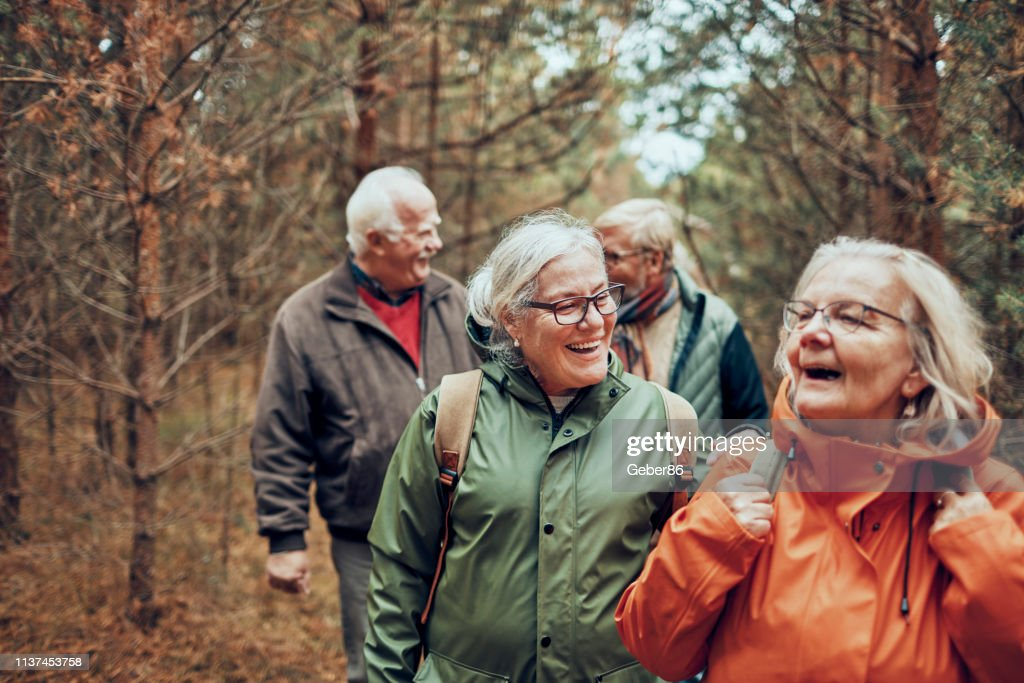 Seniors hiking through the foerst : Stock Photo