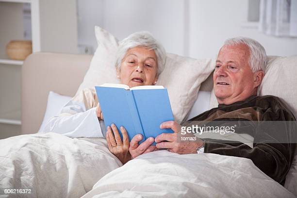 Seniors in bed reading a book