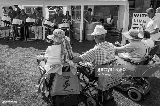 idosos de scooters para mobilidade assistir a banda no verão fair - steel drum - fotografias e filmes do acervo
