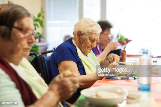 seniors in the nursing home having breakfast in the dining room - residential care stock photos and pictures