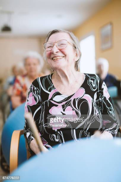 seniors in the nursing home having relaxation exercises with fitness ball - residential care stock photos and pictures