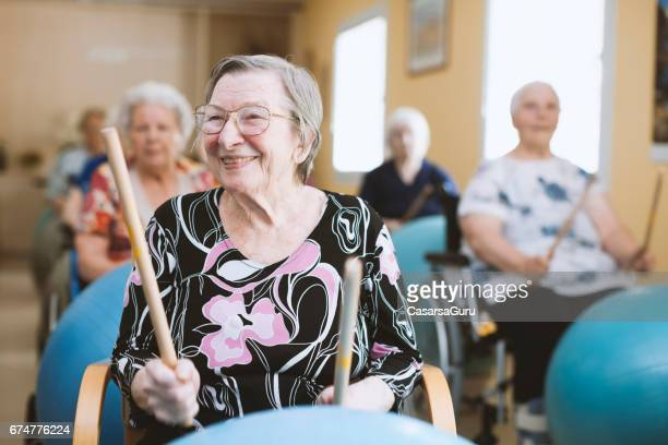 seniors in the nursing home having relaxation exercises with fitness ball - recreational pursuit stock pictures, royalty-free photos & images