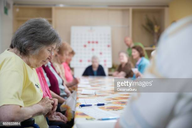 Seniors In The Retirement Community Socializing By Playing Bingo