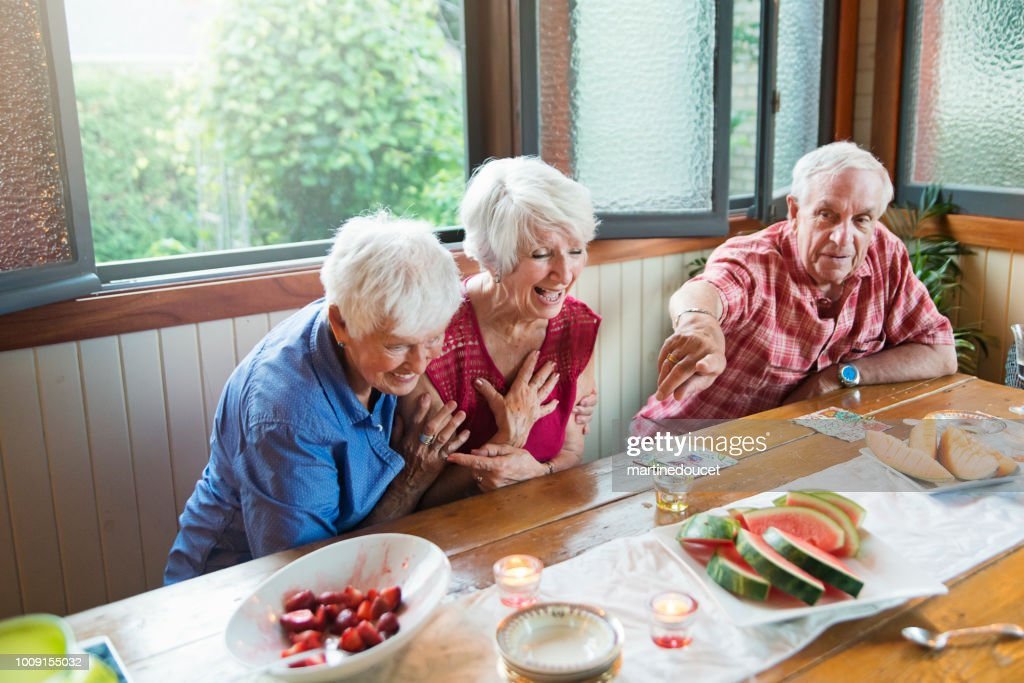 Seniors laughing at dinner in summer house. : Stock Photo