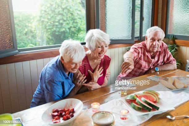 Seniors laughing at dinner in summer house.
