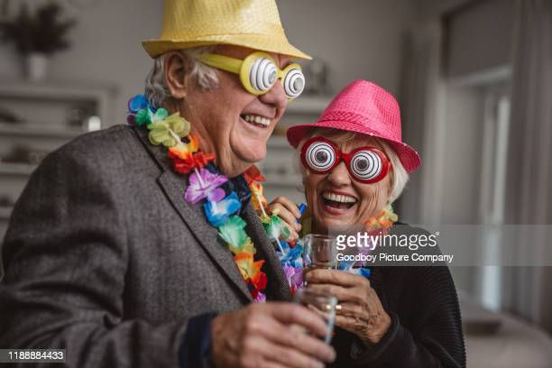 seniors laughing while enjoying themselves at a new year's party - 70 year old man stock pictures, royalty-free photos & images